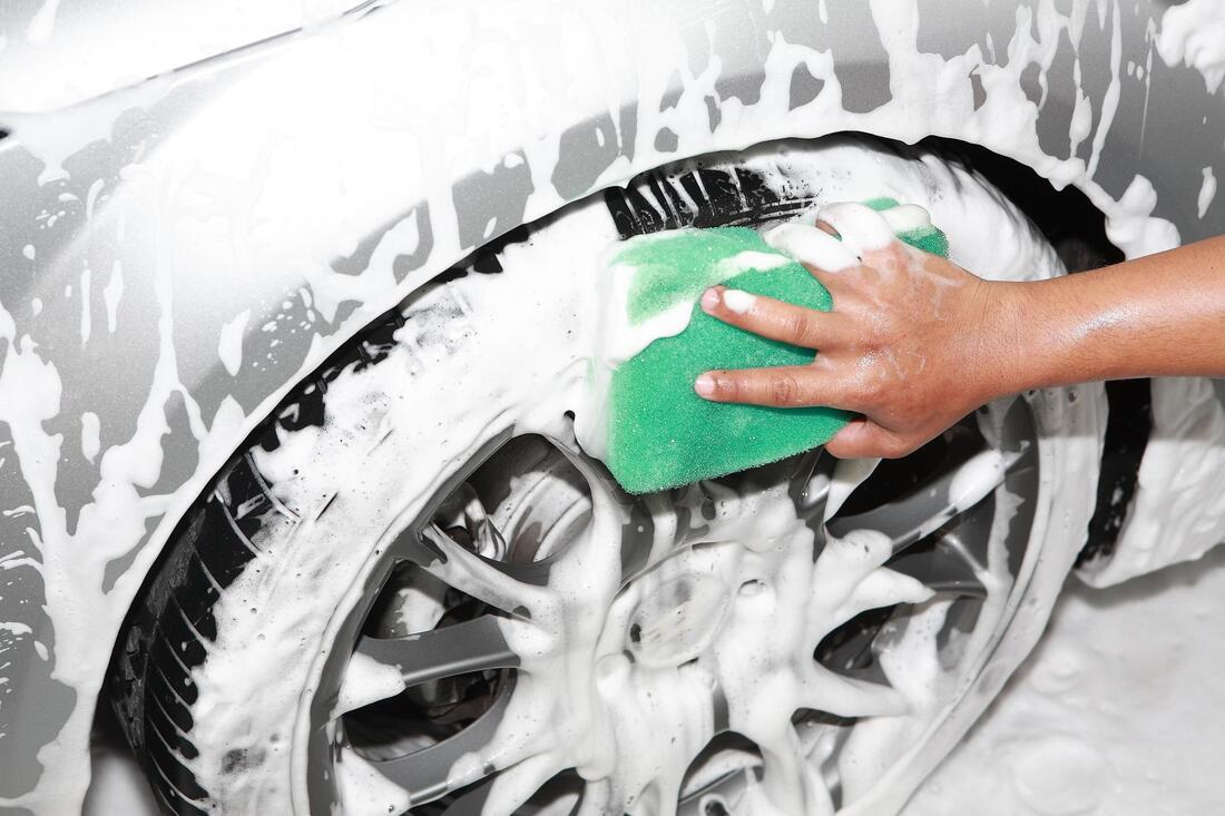 professional auto detailing expert washing tire and wheel